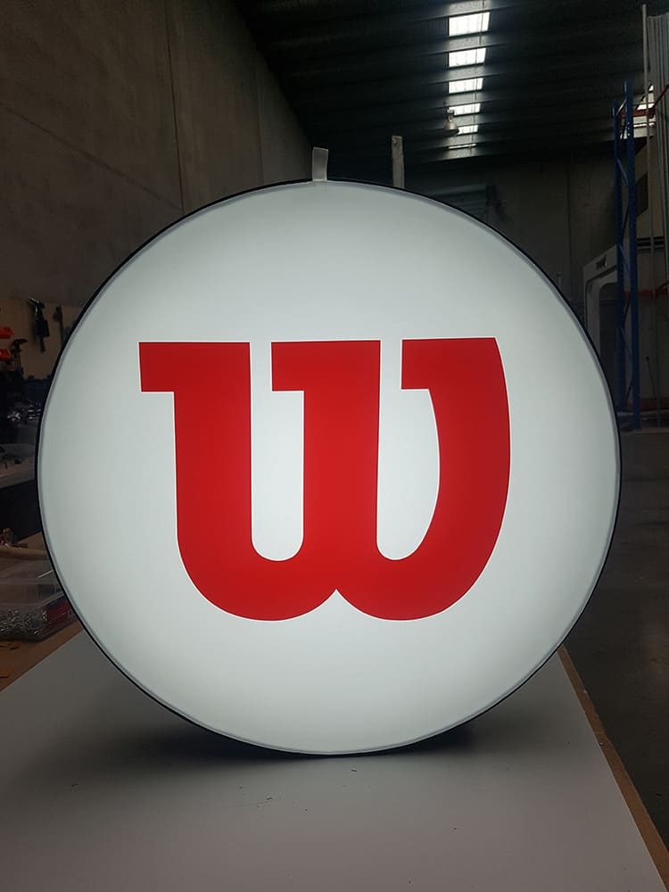 Circular backlit frame containing the red Wilson logo