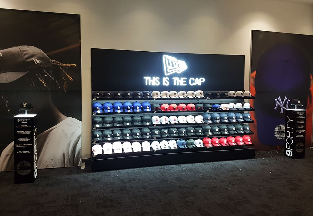 A cap display featuring 3D LED lettering glowing white with text