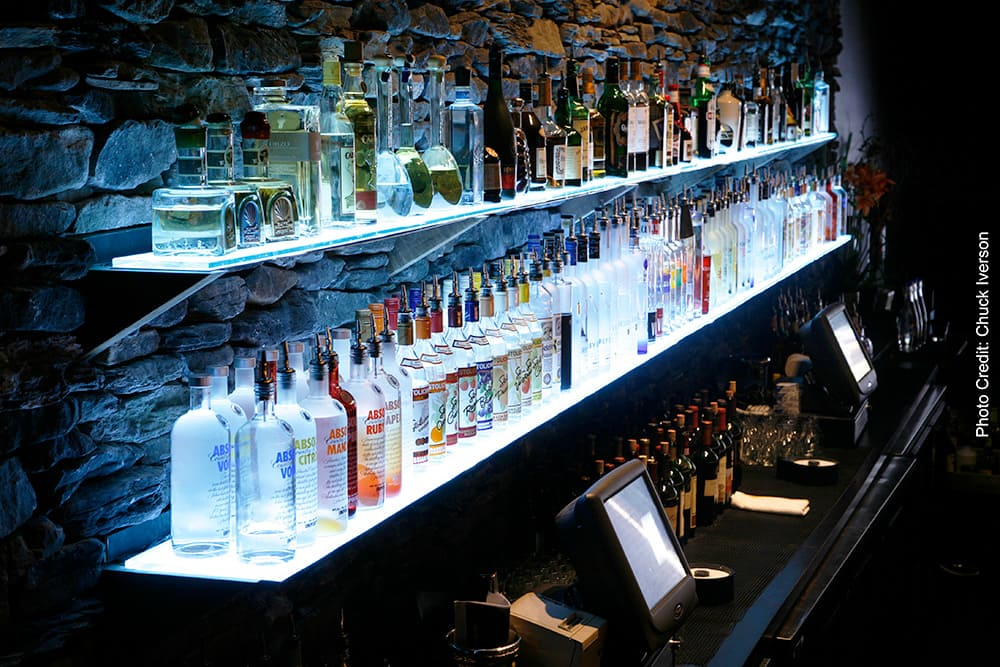 Alcohol bottles being illuminated underneath by an LED panel