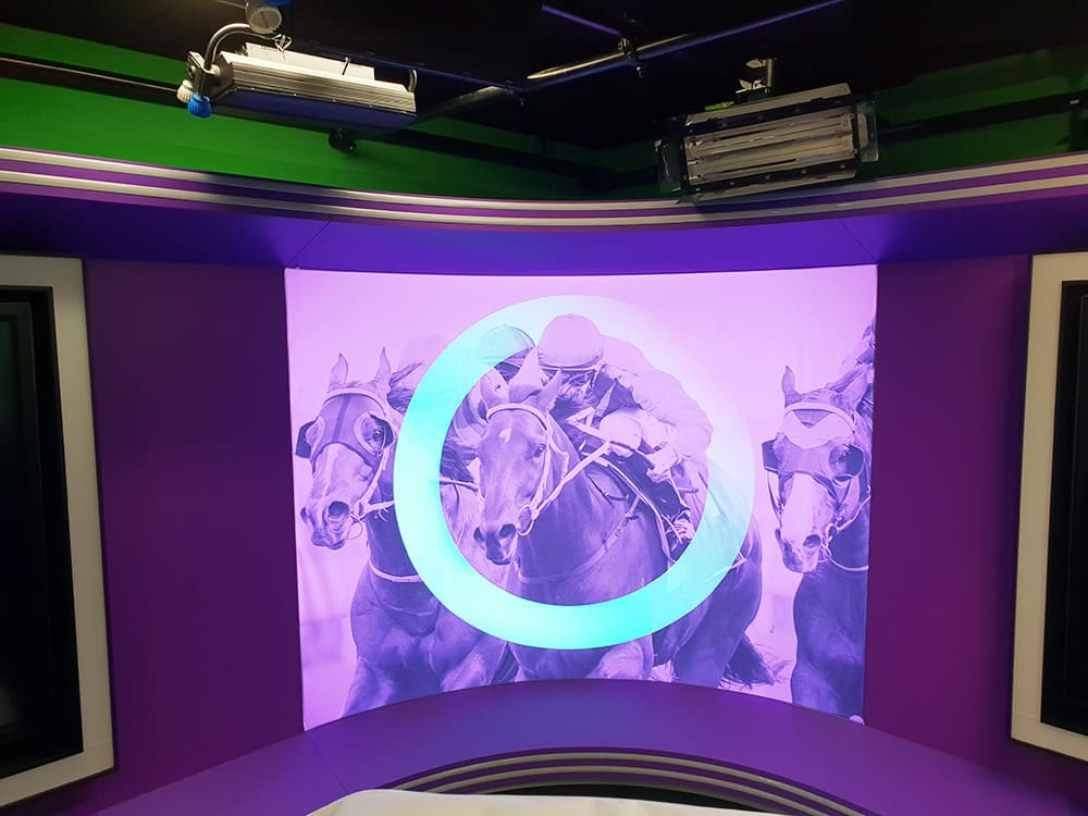Image of a jockey riding a horse on an illuminated fabric frame for TAB Sports