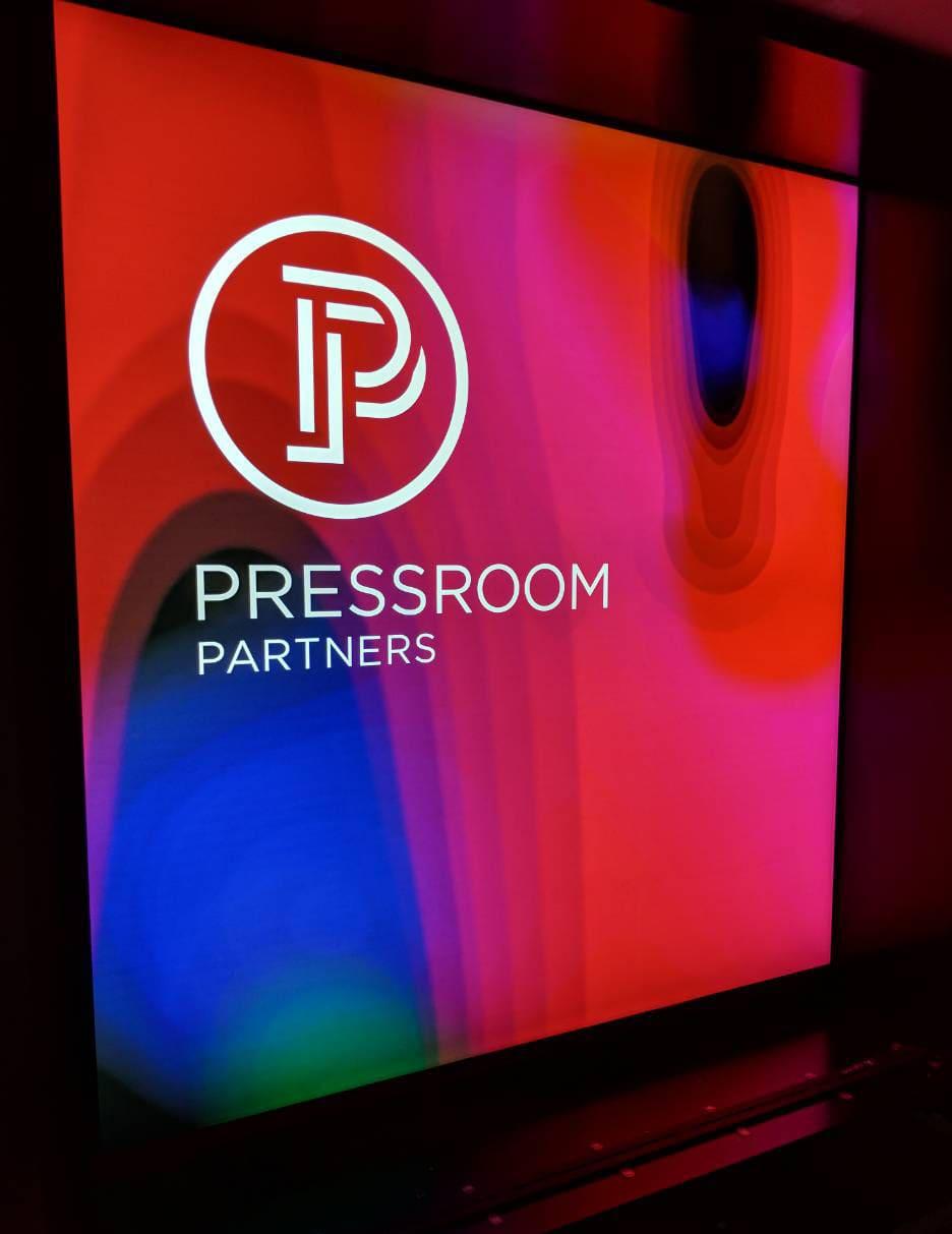 Pressroom logo on backlit pink, blue and green frame