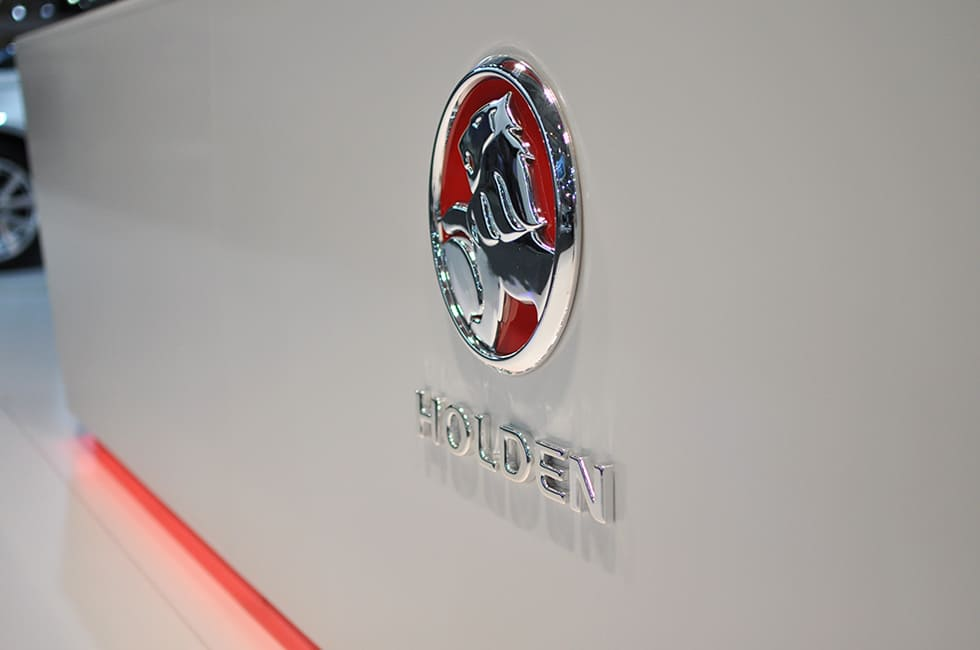 Holden logo on white background with red LED Extrusion glowing from underneath feature wall
