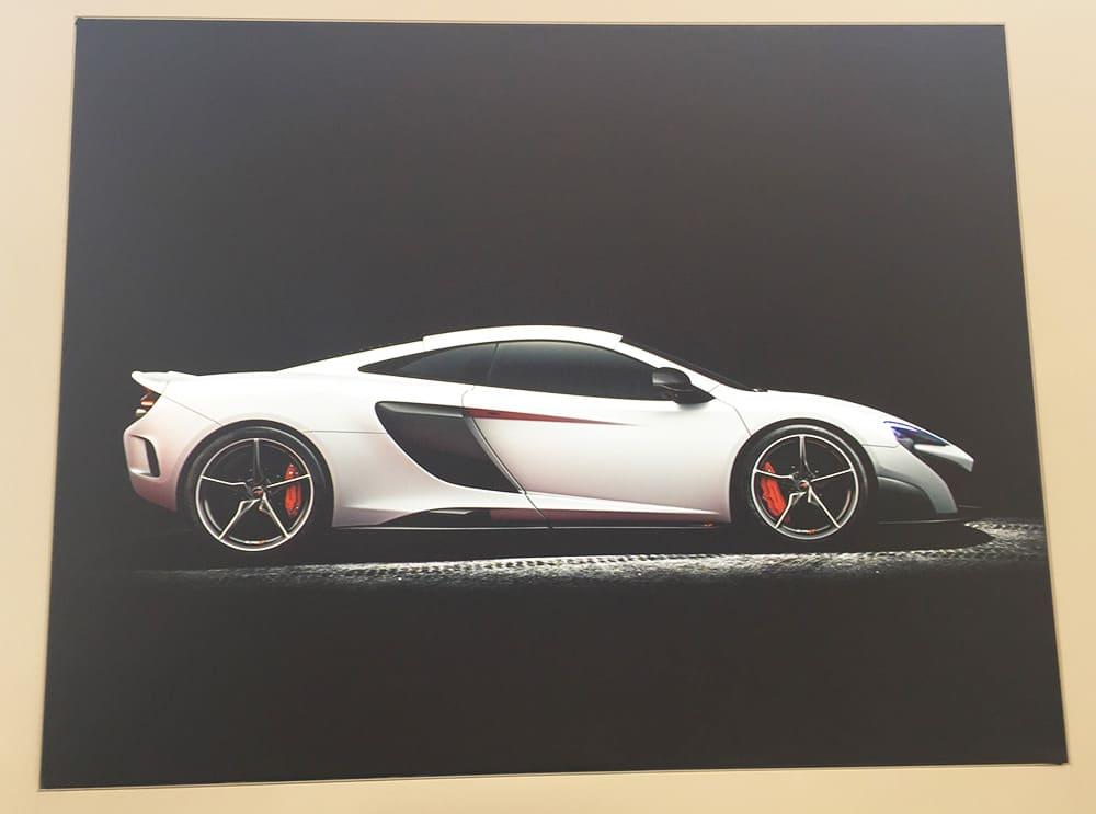 silver McLaren racing car on a black background