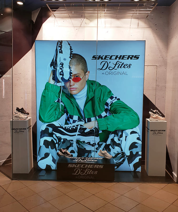 Illuminated Fabric Frame of a man in a green jacket with sneakers on his hands for Skechers