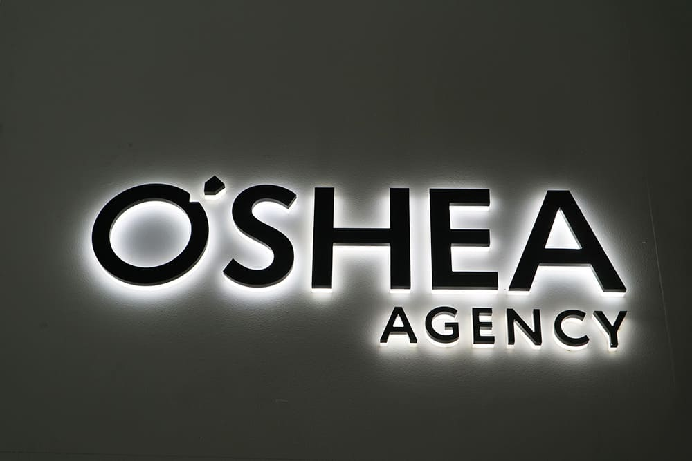 Black and white illuminated 3D lettering of O'Shea Agency logo