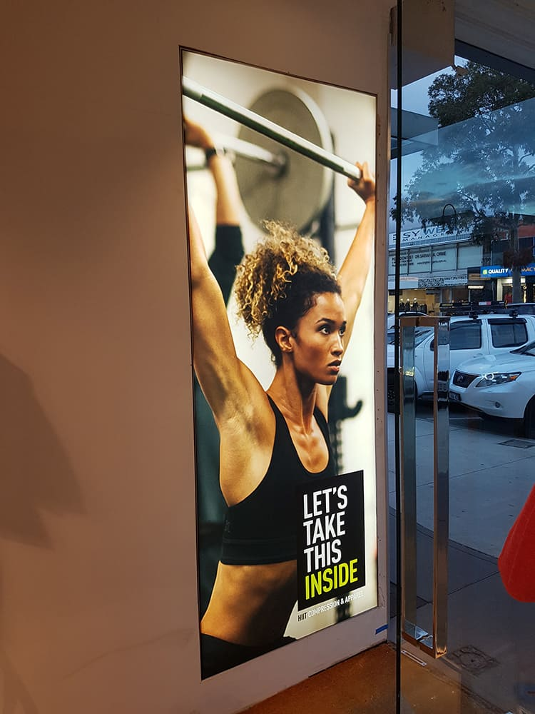 2XU promotional signage of woman lifting weights at Melbourne retail store