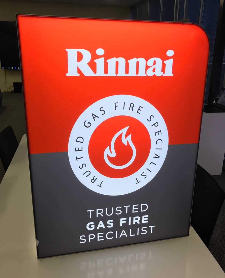 Rinnai logo and brand slogan on red, white and black backlit fabric frame